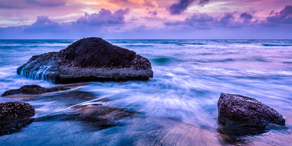 Tropical beach vacation background - panorama of waves and rocks on beach on sunset with beautiful cloudscape